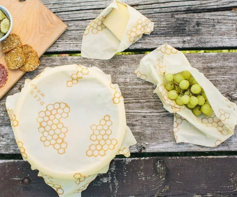 the wrap over a bowl of food and the wrap being used to hold grapes
