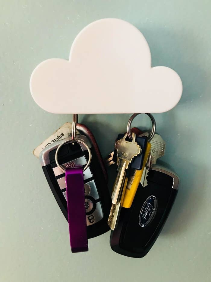 A minimalist cloud magnet tacked to a wall holding two sets of car keys