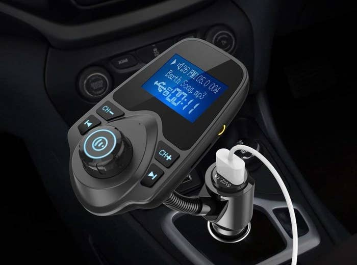 the black audio adapter plugged into a car jack with a small display screen and controls to pause and skip music
