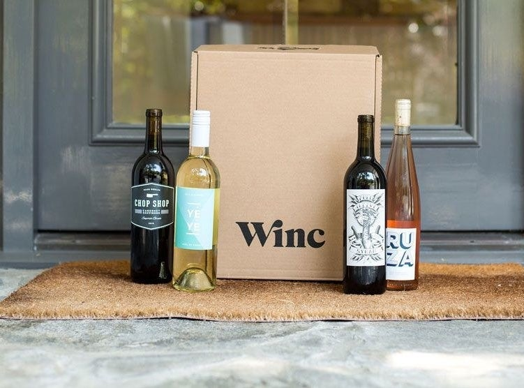 Box at doorstep with four bottles of wine beside it