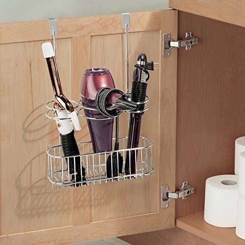 """Promising review: """"This is the most amazing invention EVER! Holds your straightener, blow dryer, curling iron or whatever else you want to store in the third slot. Now my stuff is all right there when I open the cabinet in my bathroom and the cords are not all tangled up!"""" —Abeau01Get it from Amazon for $17.99 (available in seven colors)."""