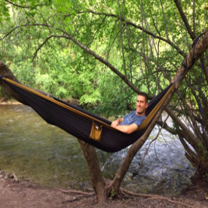 person in a hammock by a river