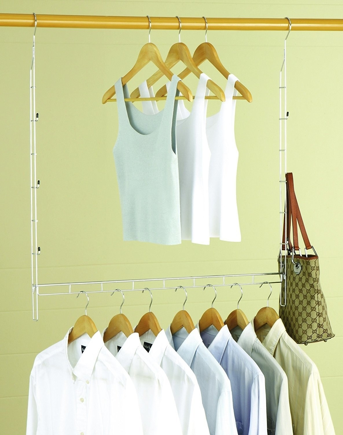 The bar with shirts on hung below a closet rod