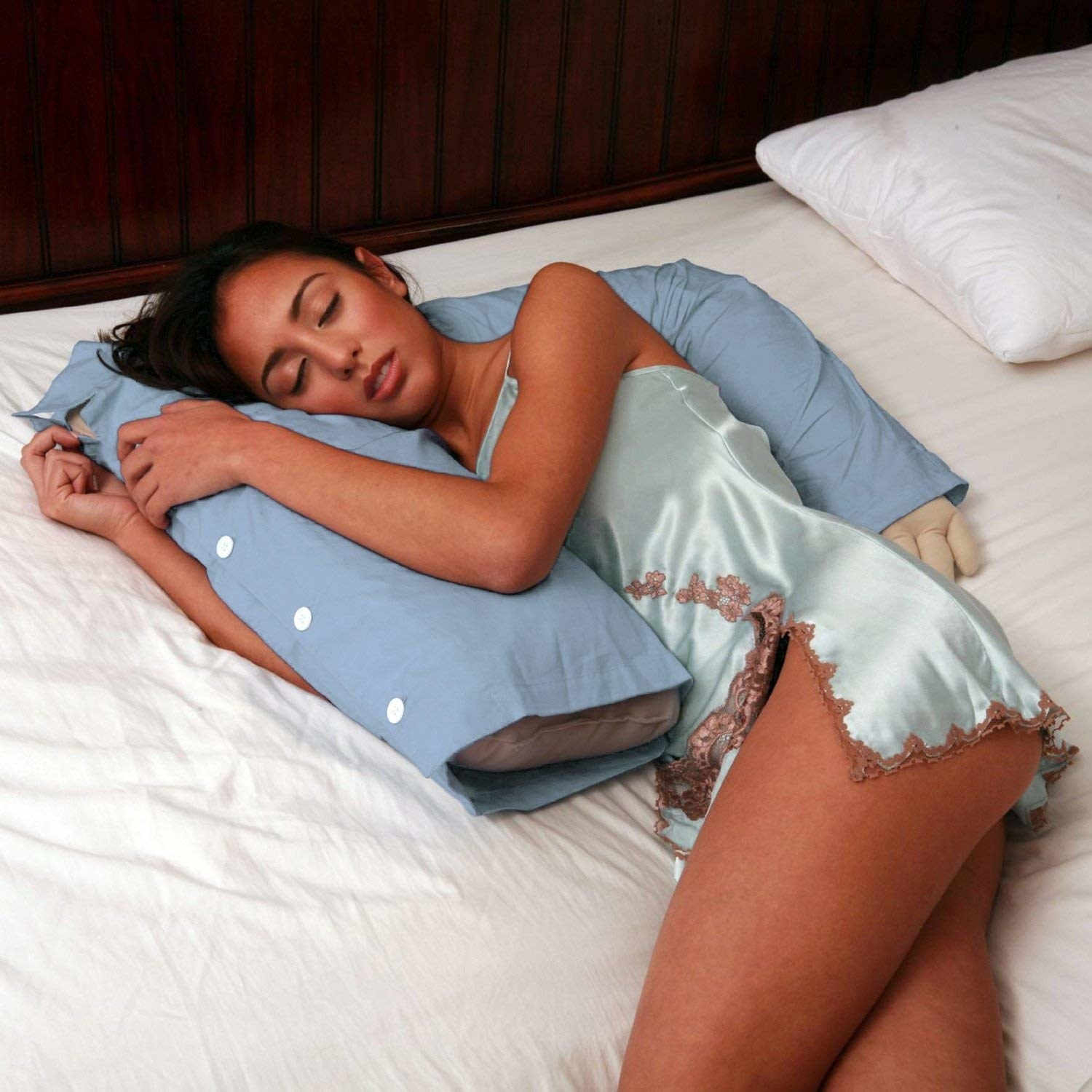 A model being spooned by the pillow shaped like a torso with an arm