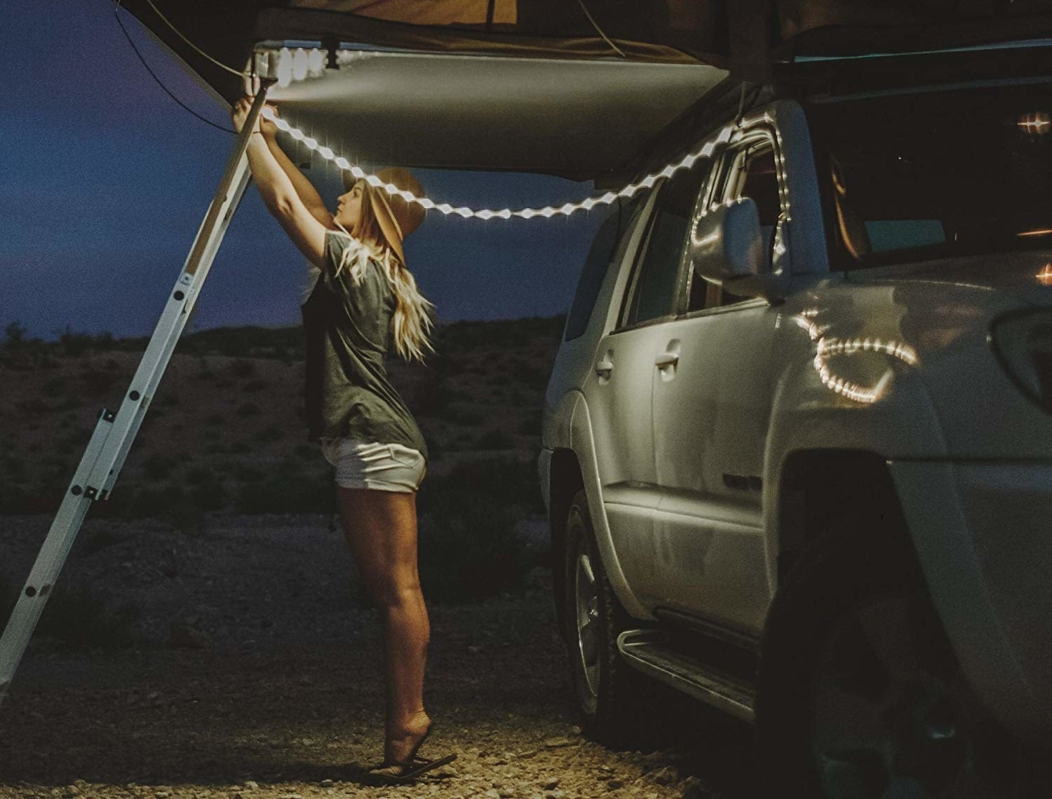 person hanging up a string of lights on a camping van