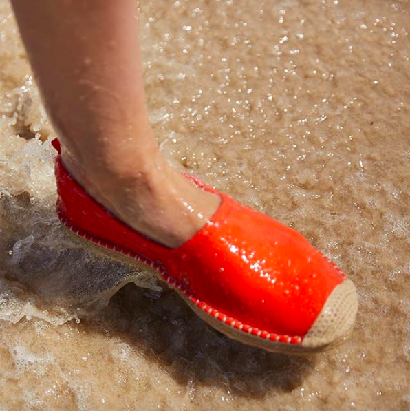 foot wearing the espadrille show in the ocean water