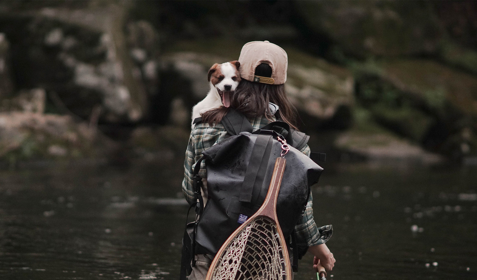 person holding a dog in their arms with the pack on their back by a river