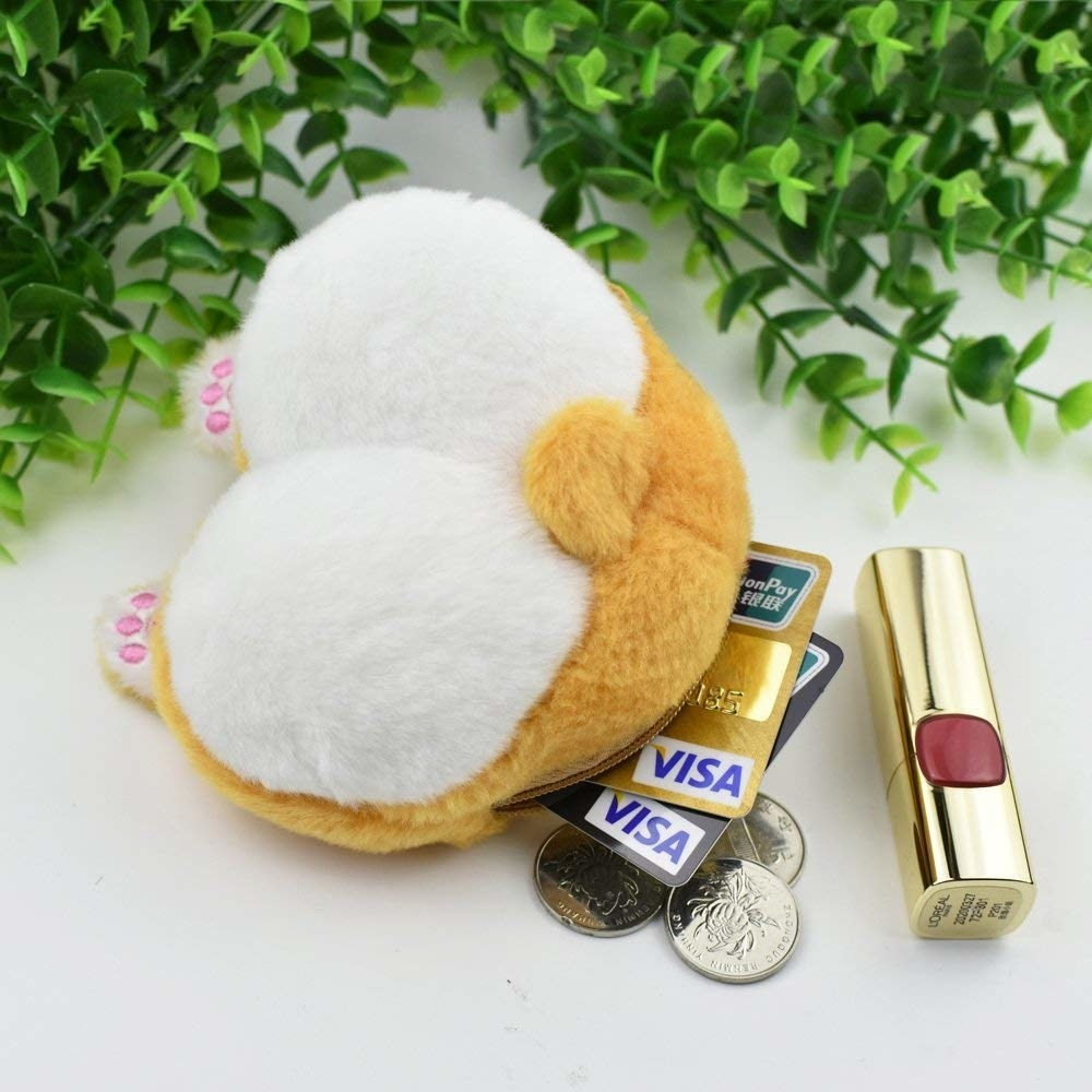 The furry coin purse with tail, little paws, and showing it fitting a lipstick, two credit cards, and coins