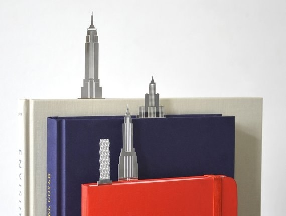 three books with skyscraper-look bookmarks marking pages