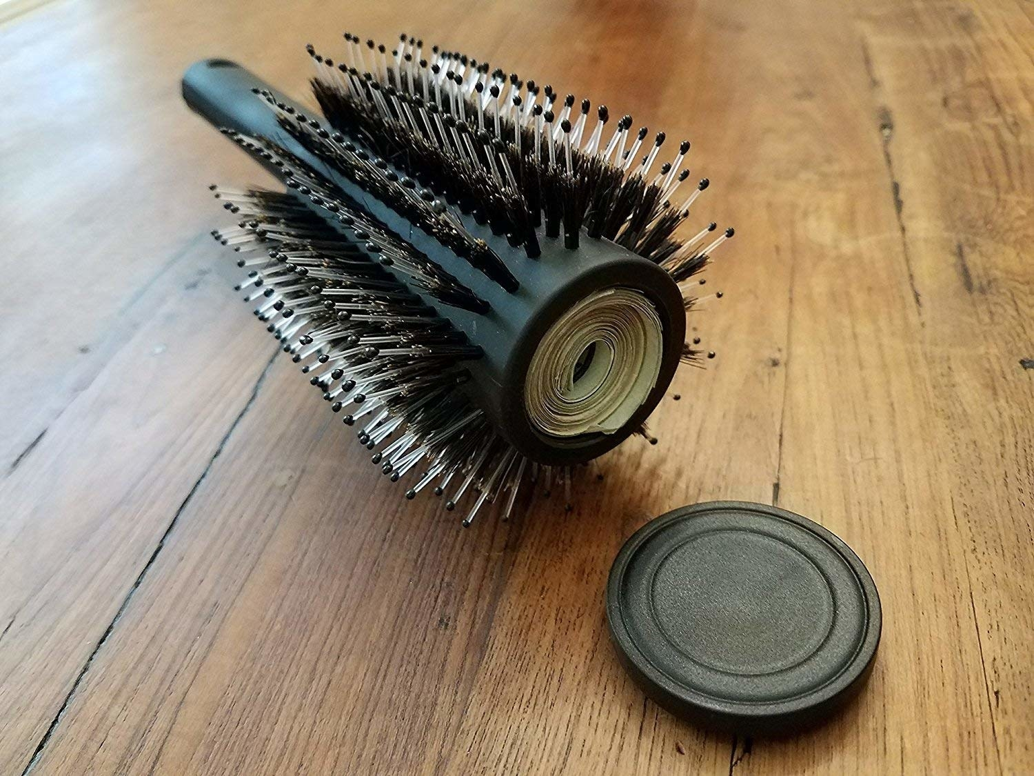 round hairbrush with part inside for stashing cash