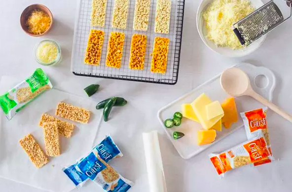 Baked cheese bars in and out of packaging around table of ingredients