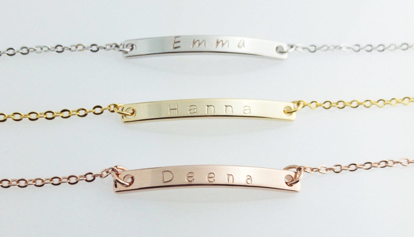 Three bracelets with name bars in silver, gold, and rose gold