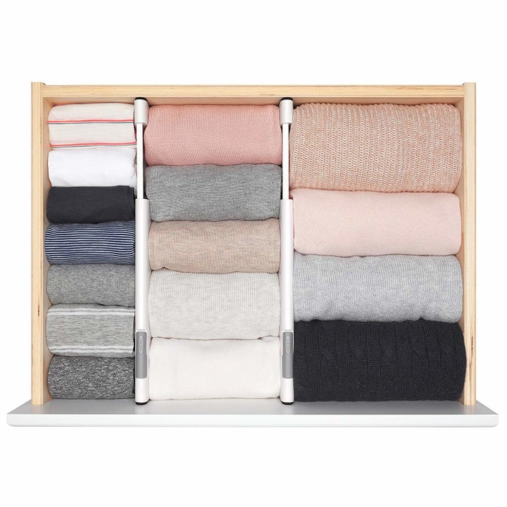 A top-down of a dresser drawer divided into thirds, with different-width folded garments in each