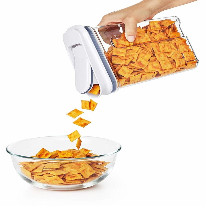 A hand pouring cheese crackers out of one of the containers, it's lid flipped open for easy pouring