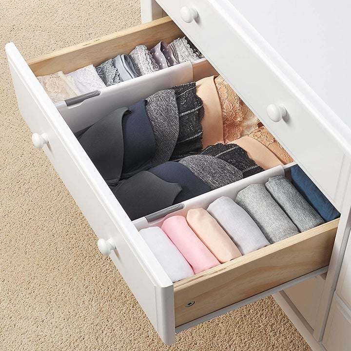 A dresser drawer neatly divided into thirds, with folded underwear on one side, a stack of bras in the middle, and other folded garments on the other end