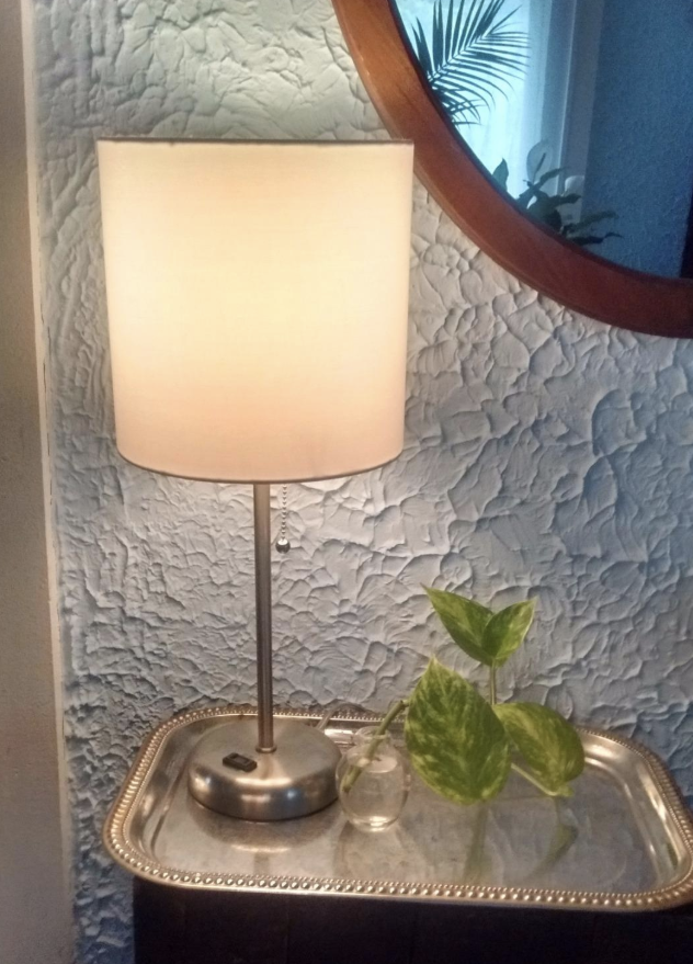 Reviewer photo of the lamp with a silver base sitting on a bedside table
