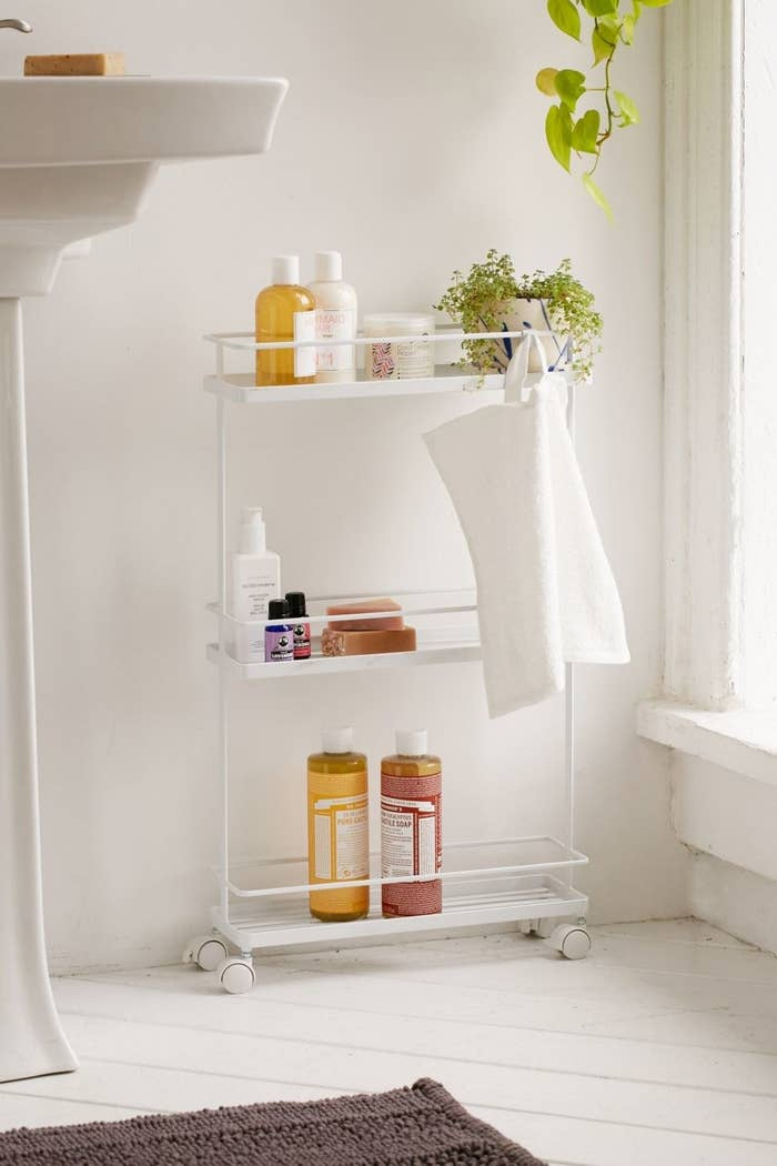 The rolling cart holding a variety of bath items in the bathroom