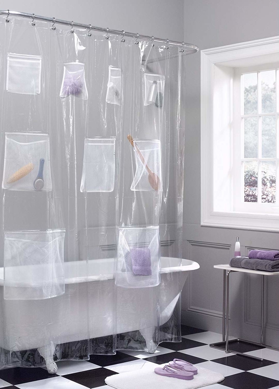 clear shower curtain with mesh pockets filled with towel, shampoo, brush, and other items