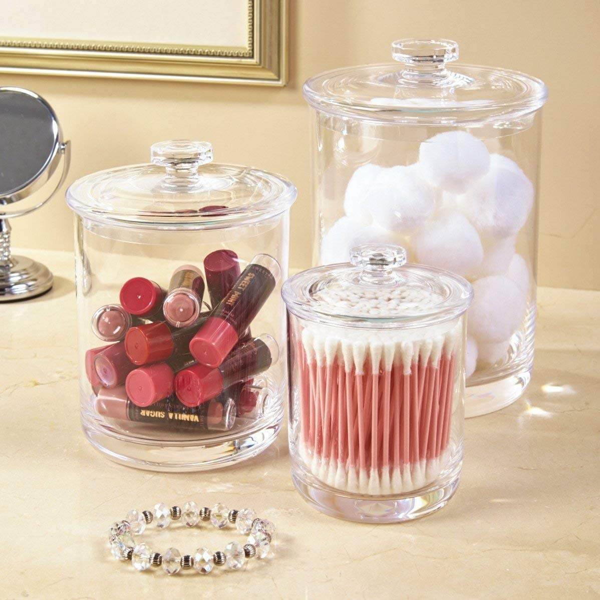 Three different sized jars holding cotton swabs, puffs, and other items