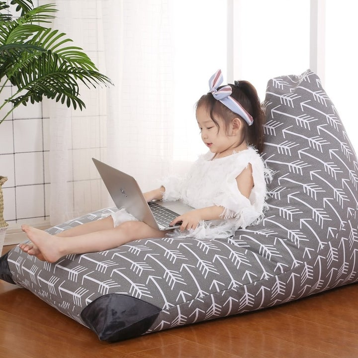 A child model sits on the beanbag, which is stuffed full, and has a capital L-shape, if the L turned on its side, so there's a short back and a long seat