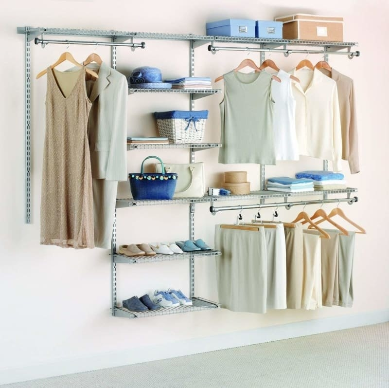 The system with three different areas to hand things and seven shelves of different lengths attached to a wall with clothes, shoes, and accessories in it