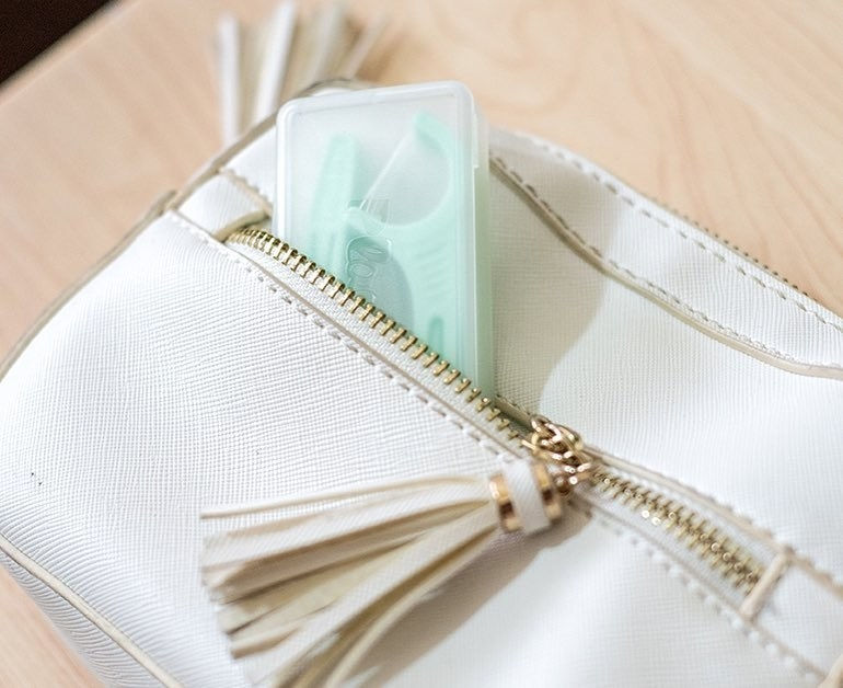 case of floss picks fits in the small pocket of a clutch