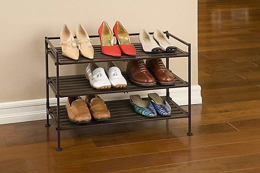 A three-tier shoe rack with seven pairs of shoes on it