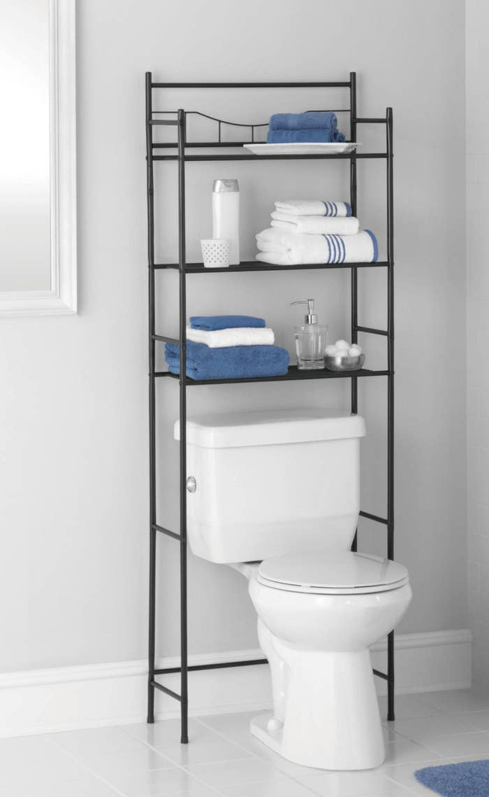 The shelf  holding various items over the toilet