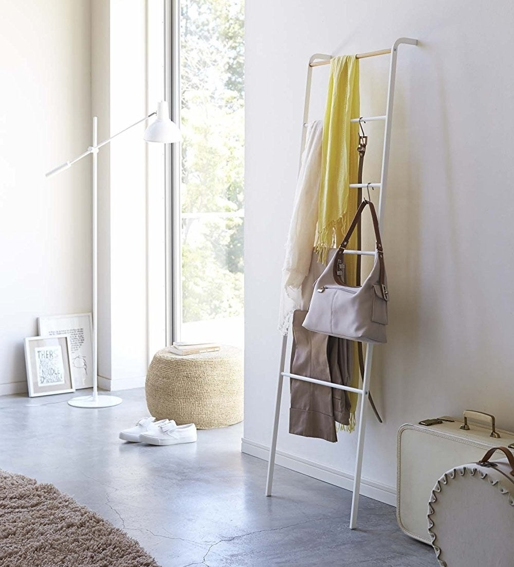 The ladder holding blankets, a bag, a belt, and more