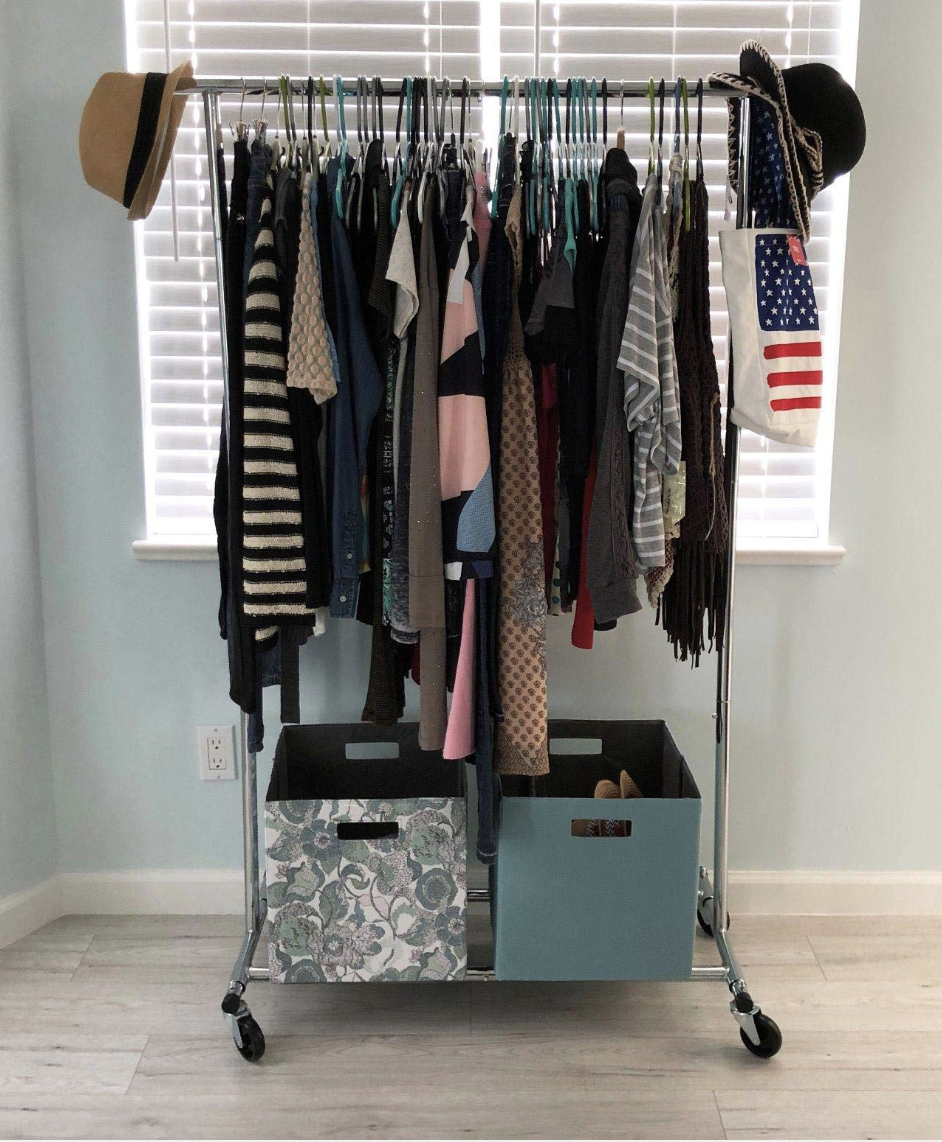 Reviewer photo of the rack  with lots of clothes hung on the rod, accessories handing from the ends and two cubes at the bottom holding shoes