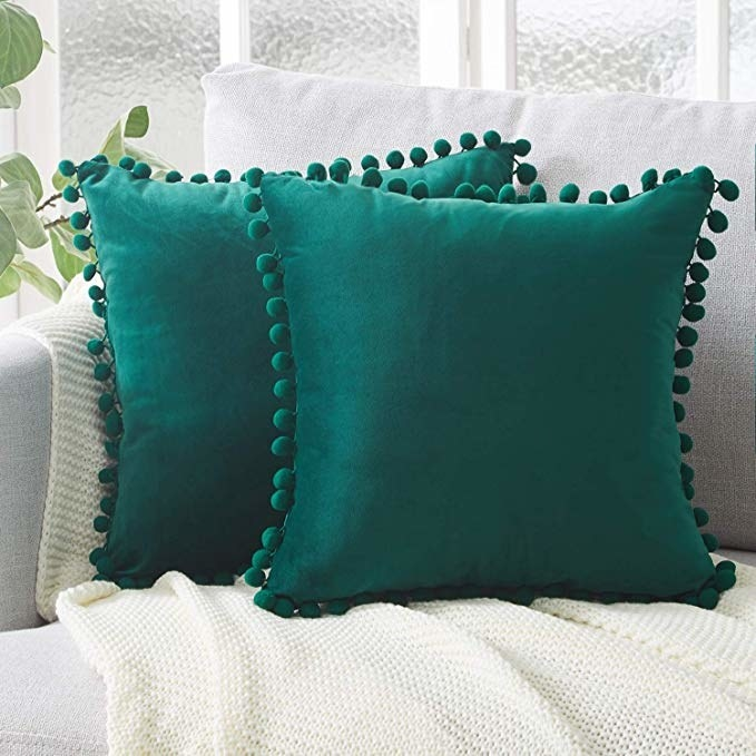 Emerald green pillow covers with pom pom accents bordering entire pillow