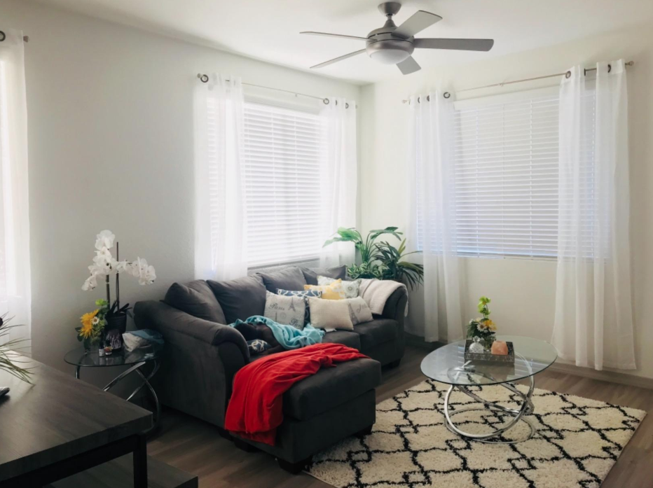 Reviewer's living room with sheer curtains hung on each window that creates a light air vibe