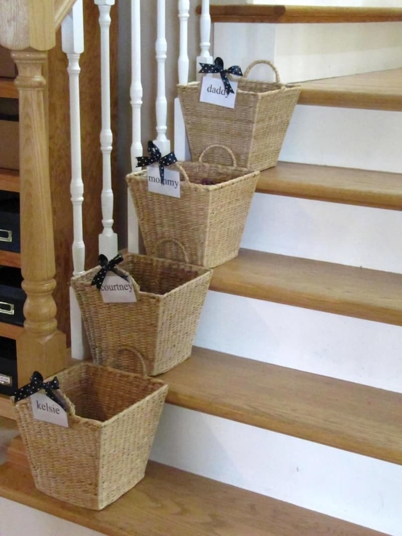A blogger's photo of four baskets on their home's stairs, one basket per step, each with a different family member's name on it