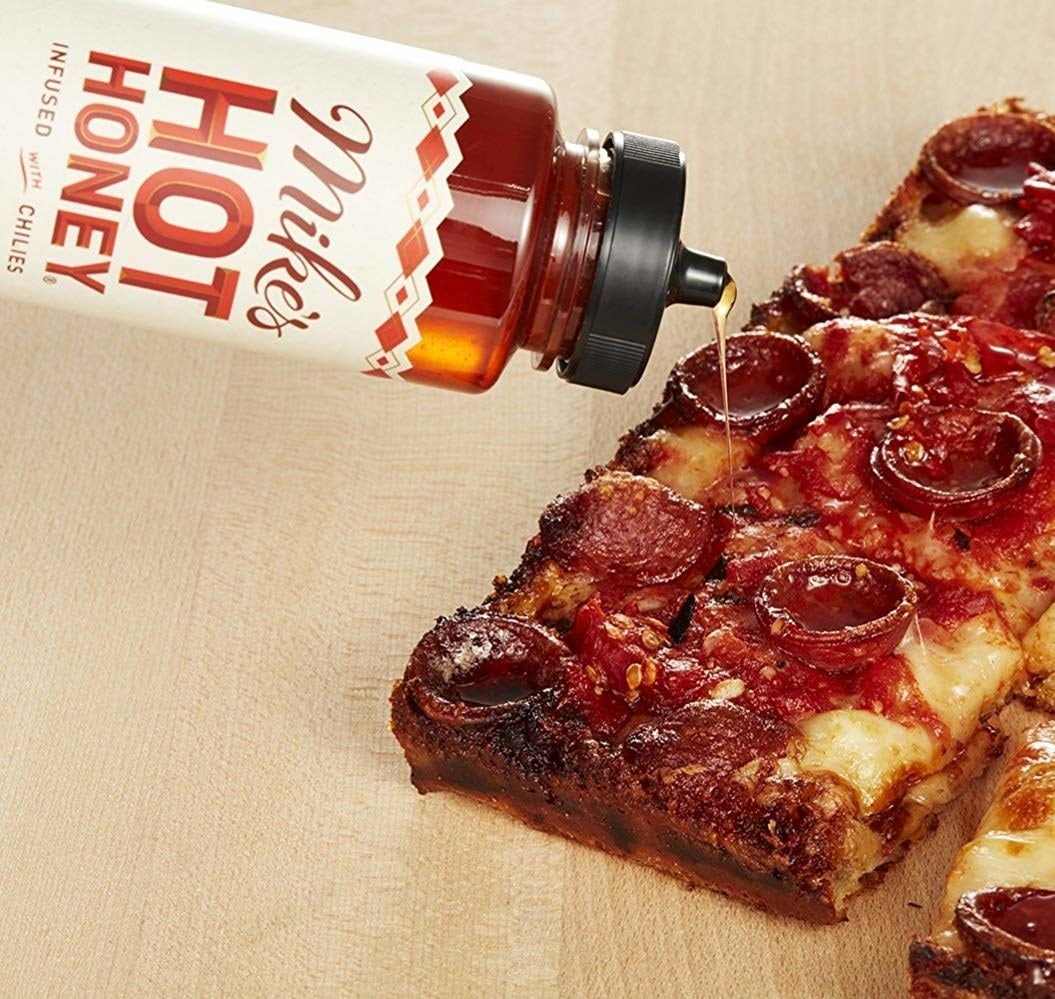 mike's hot honey being drizzled on pizza