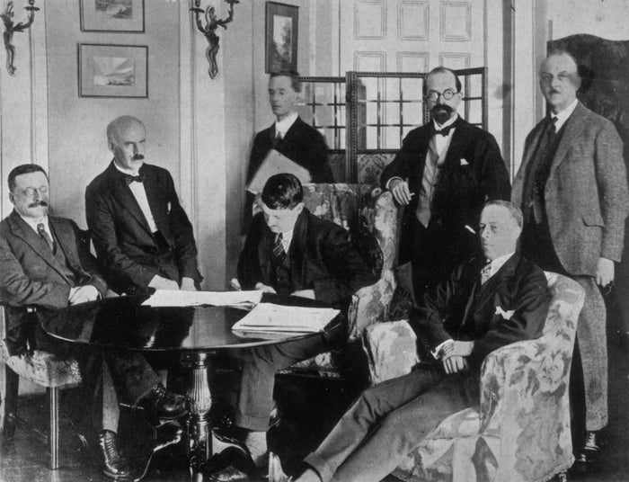 1921: Members of the Irish delegation at the signing of the Irish Free State Treaty between Great Britain and Ireland. The delegation includes (seated from left) Sinn Féin founder Arthur Griffith, E.J. Duggan, Irish Minister for Finance Michael Collins, politician Robert Barton, author Robert Erskine Childers (standing from left), lawyer George Gavan Duffy, and John Chartres.