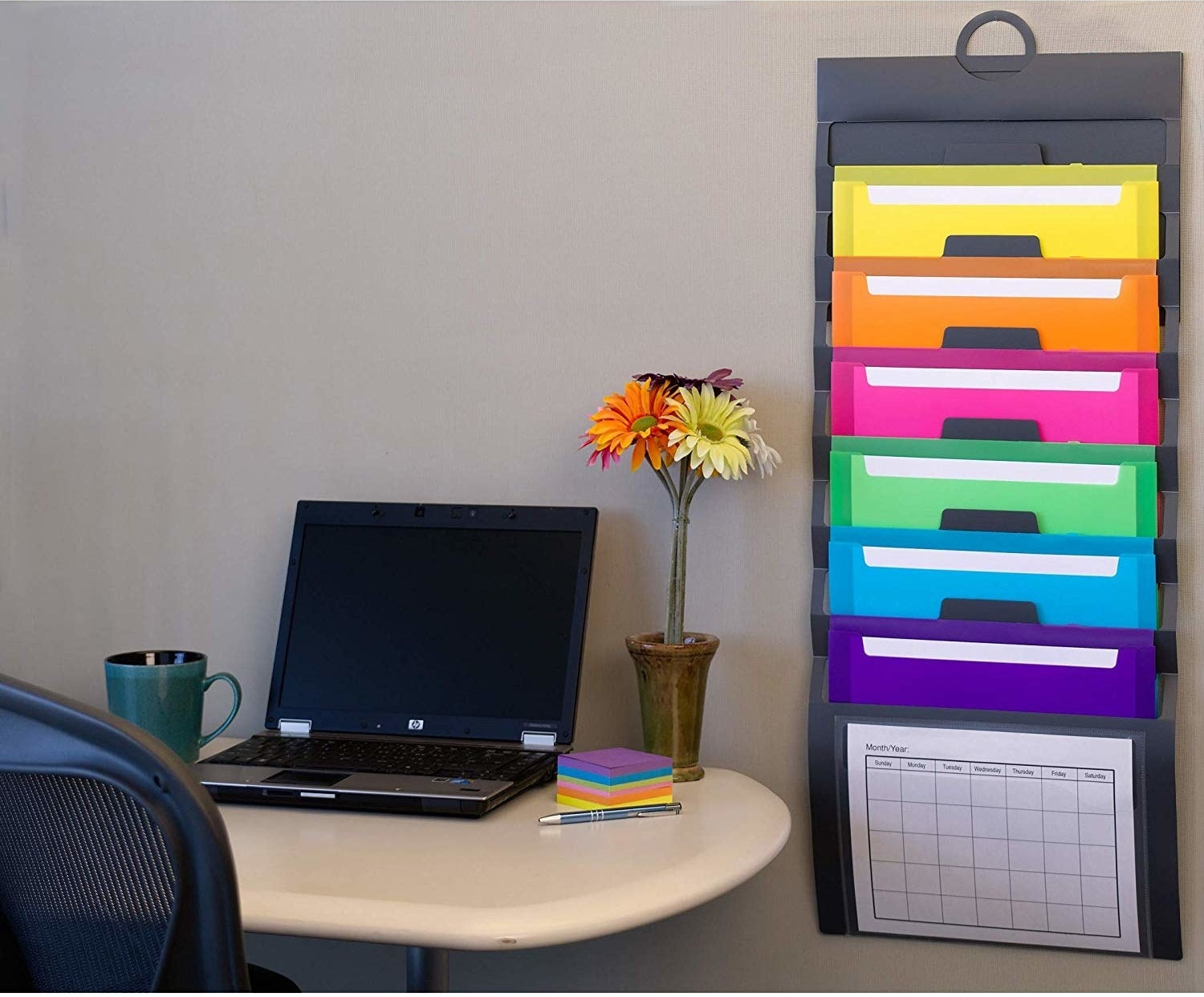 The organizer next to a desk. It lies flat against the wall, with yellow, orange, pink, green, blue, and purple pockets in addition to the clear one