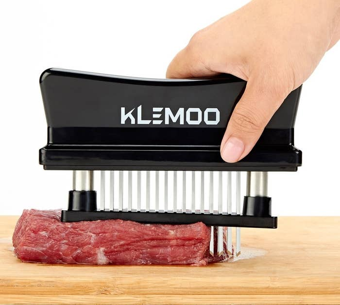 A model holding a device with spikes that are being pressed into a slab of meat
