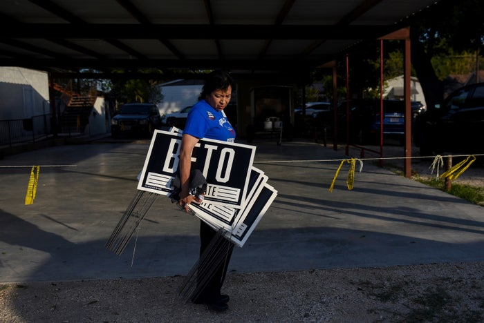 Juanita Martinez, secretary of the Democratic Party in Eagle Pass, Texas, carries a handful of yard signs as O'Rourke hosts a town hall Aug. 4, 2018, at Plaza Hall in Del Rio.