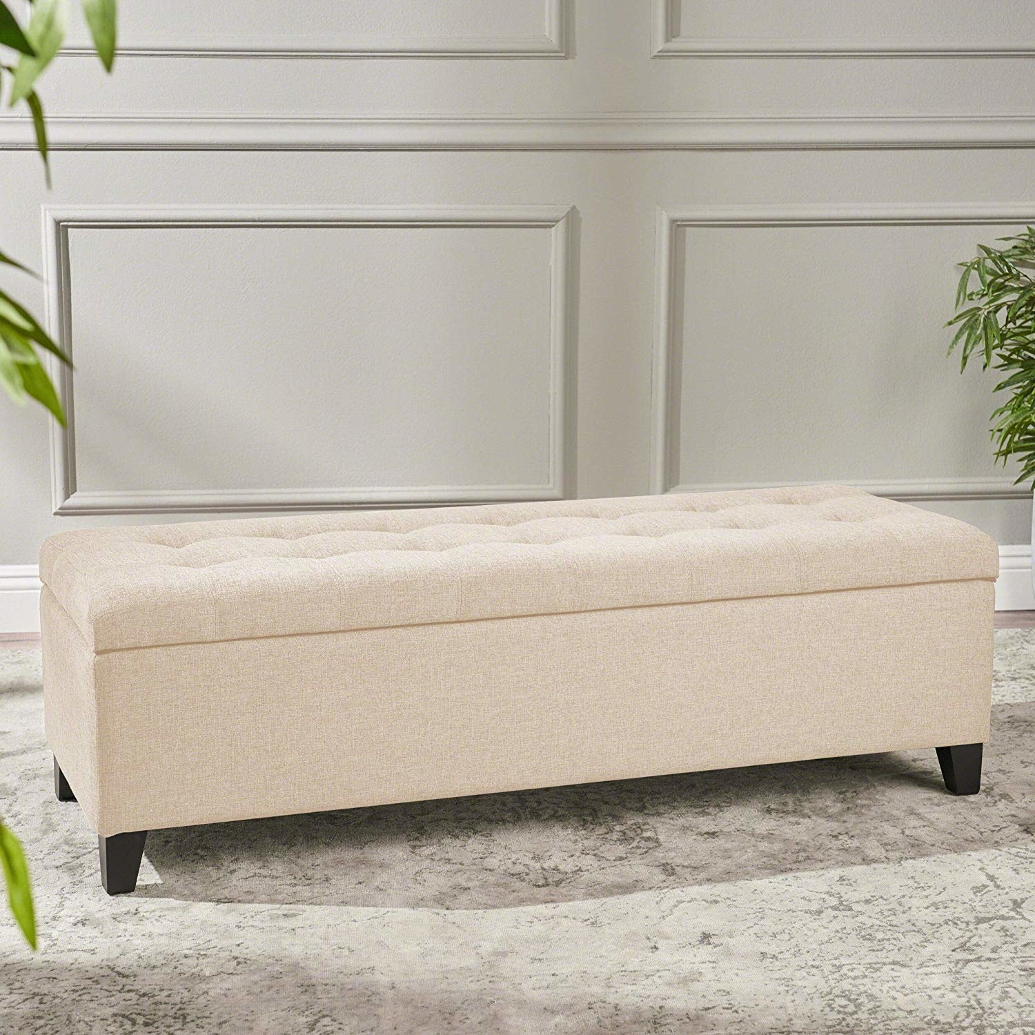 A taupe tufted storage ottoman with tapered legs