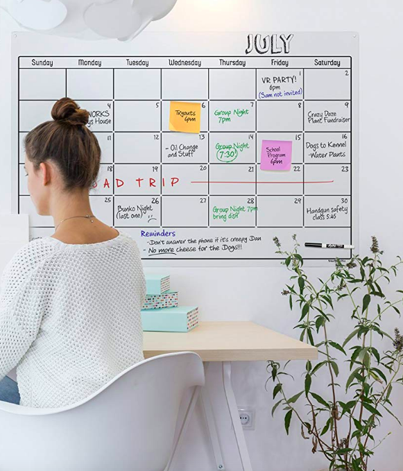 Large, clear, calendar on wall with info written with dry erase markers