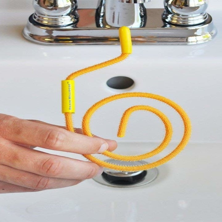 person holding up the coiled hair remover in front of a sink