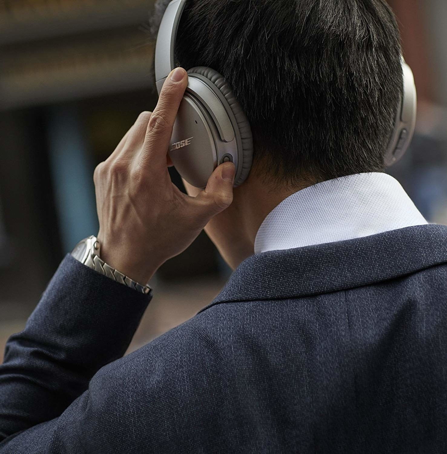 A person turning their headphones on with the buttons on the left ear