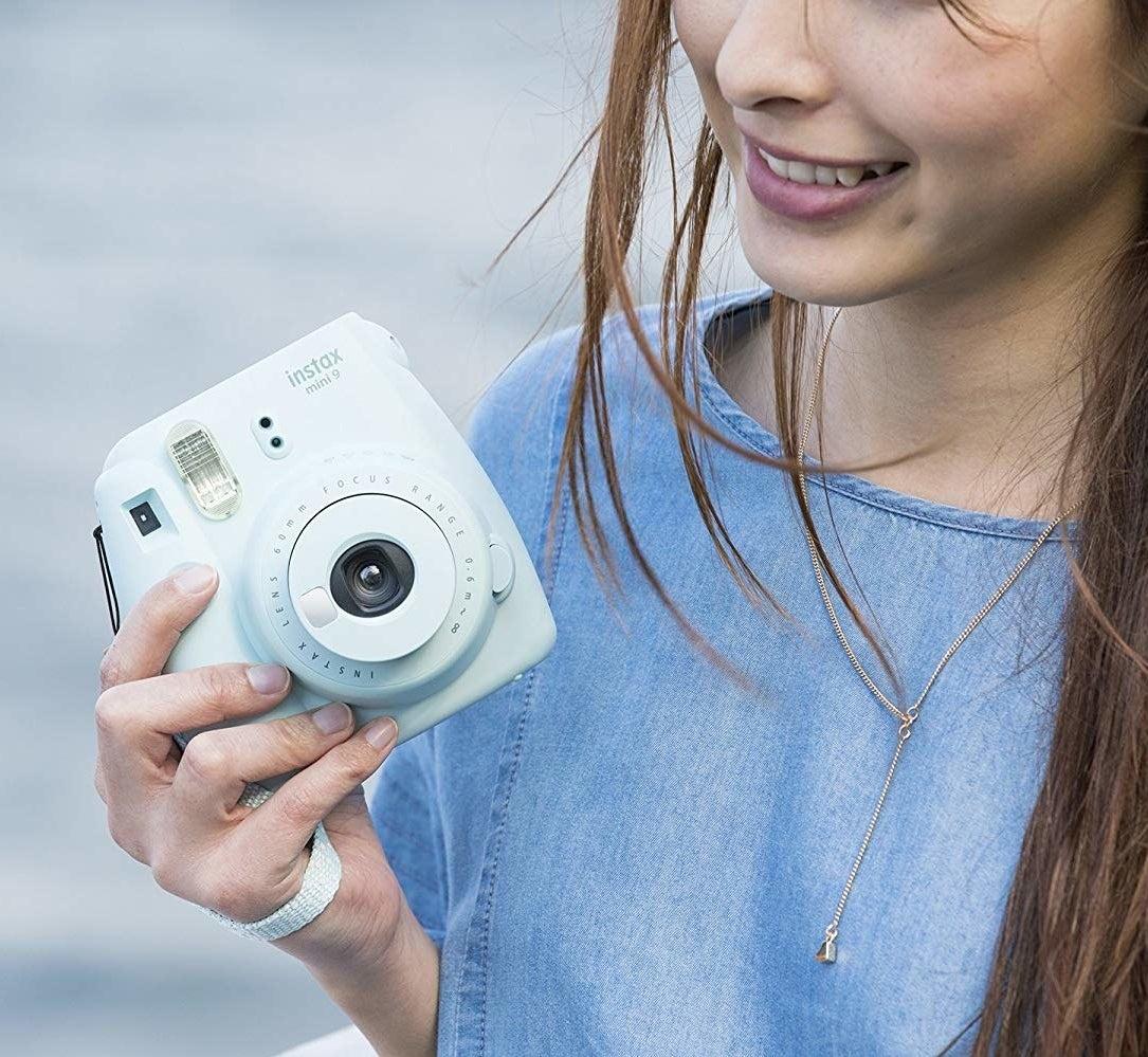 model holding light blue square instax camera