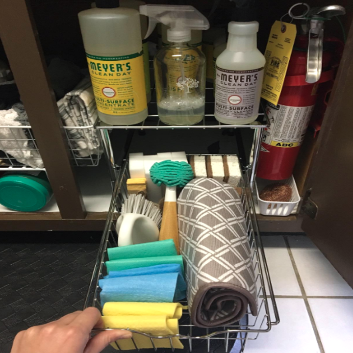 A reviewer photo with sponges, cleaning cloths, a scrub brush, Magic Erasers, and a dish-drying cloth all organized in the drawer, with bottles and spray bottles on the shelf