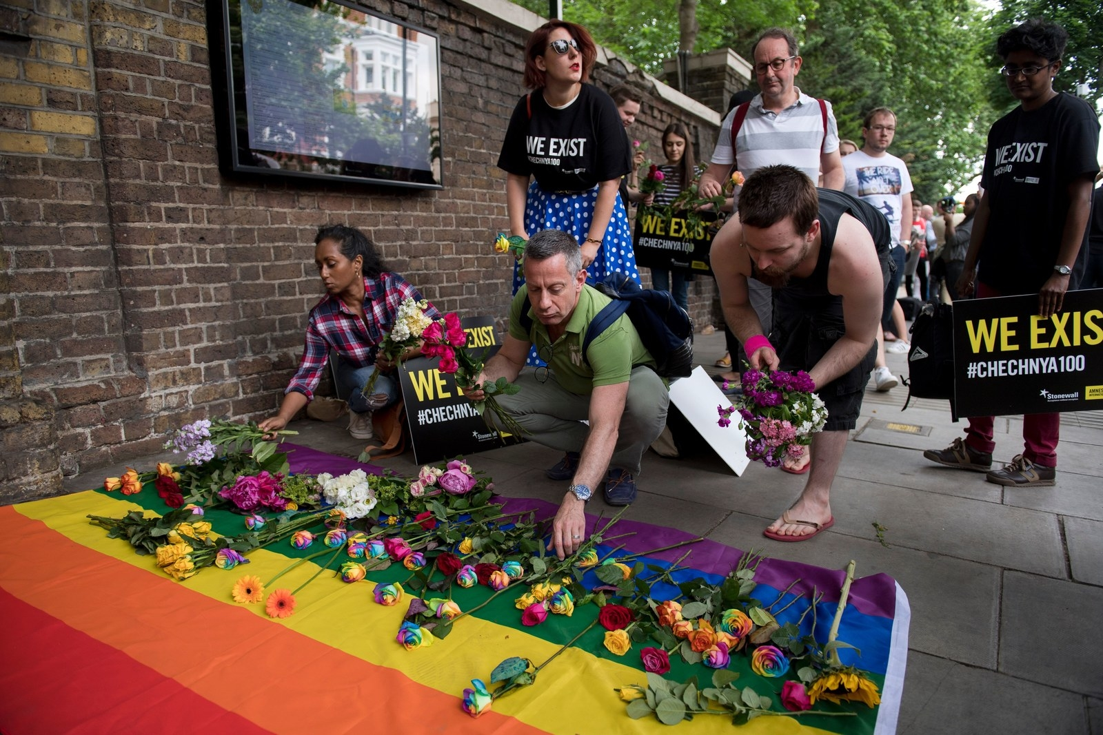 Demonstrators lay roses on a rainbow flag as they protest over a crackdown on gay men in Chechnya outside the Russian Embassy in London on June 2, 2017.