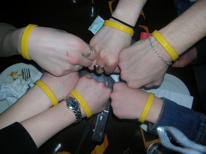 six people making a fist circle all wearing LiveStrong bracelets