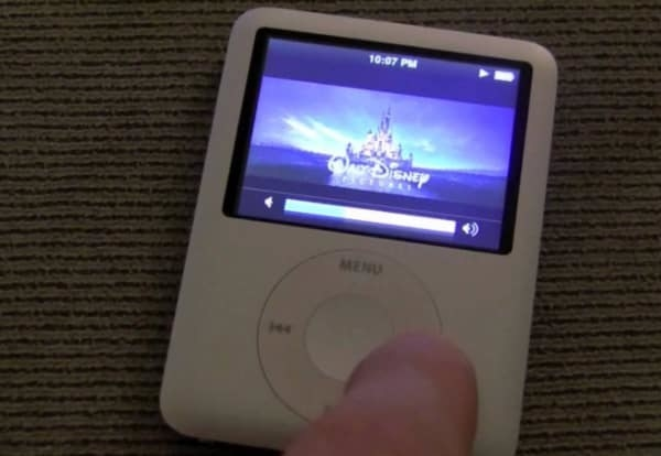A finger pushing the forward button an iPod Mini that is playing a Disney Movie