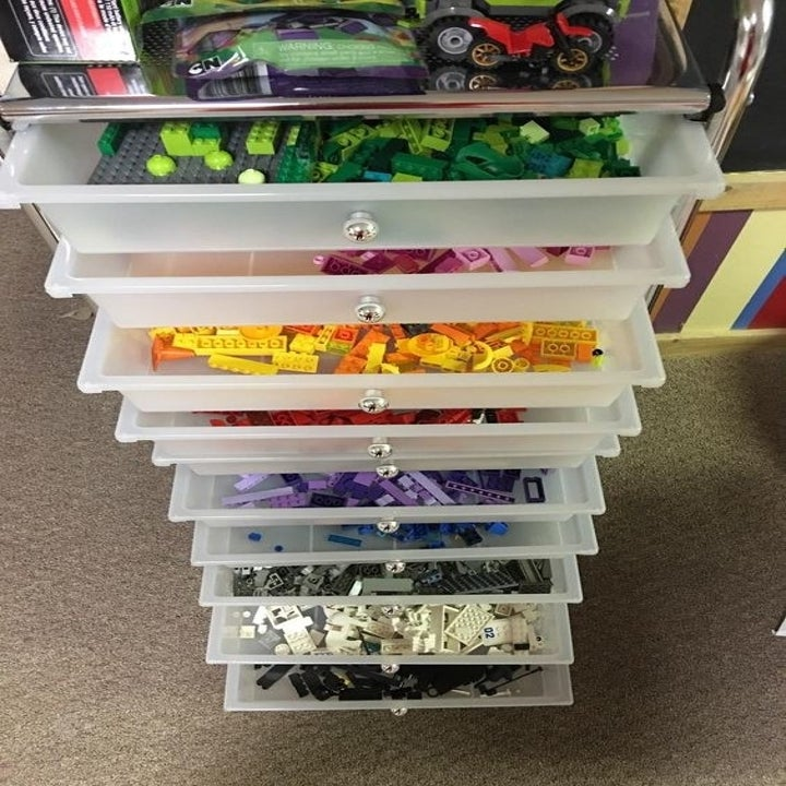 Reviewer photo of the tower, with each shelf holding different colored Lego bricks.