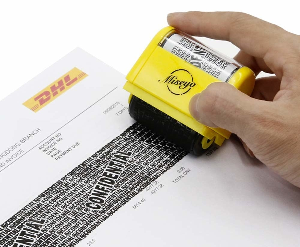 A person using the roller stamp to block out information on a piece of paper.