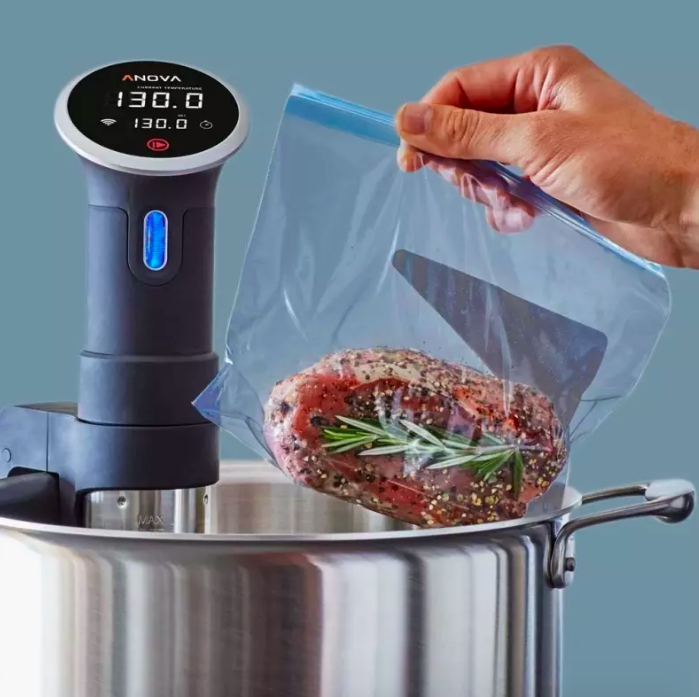 Steak being cooked in pot and baggie with tool inserted in pot